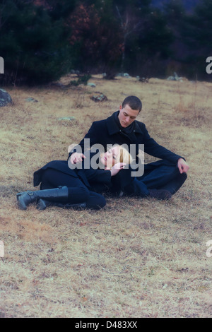 a couple in black clothes is lying on a meadow in winter - Stock Photo