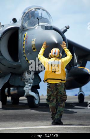 A Sailor directs an AV-8B Harrier. - Stock Photo