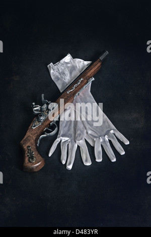 an old military rifle with white gloves - Stock Photo