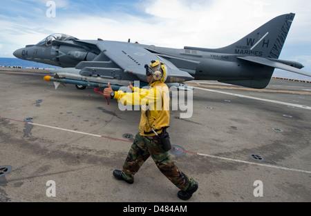 Sailor directs jet on flight deck. - Stock Photo