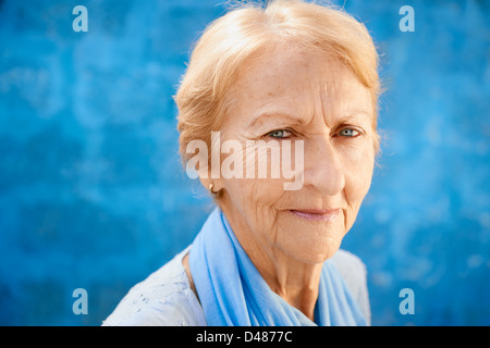 Senior people portrait, happy old blonde woman in blu clothes smiling and looking at camera against blue wall - Stock Photo