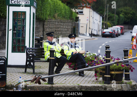 Two Irish Gardai sitting on a park bench in the picturesque village of Enniskerry in Wicklow Ireland - Stock Photo