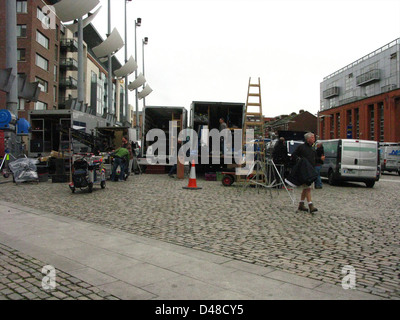 A film set with film equipment and rigs/rigging and transport trucks in Smithfield Square Dublin, Ireland - Stock Photo