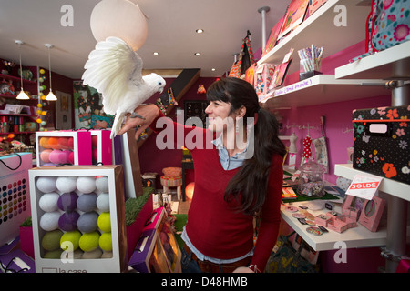 At Vichy, a young woman with her bare-eyed cockatoo (Cacatua sanguinea) in a shop of decoration and fashion accessories - Stock Photo