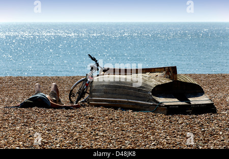 Person sunbathing with head covered on the beach at Hove, East Sussex - Stock Photo