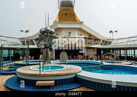 The empty chairs and sunloungers around the Crystal Pool and bar on the deserted Lido Deck of the Artemis - Stock Photo