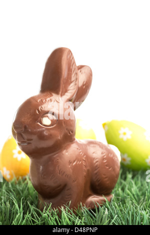 Chocolate bunny rabbit sitting on grass with easter eggs behind - Stock Photo