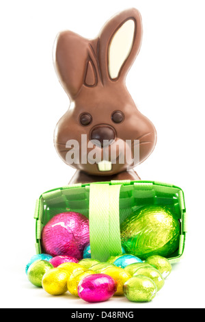 Easter eggs spilling from a basket with chocolate bunny - Stock Photo