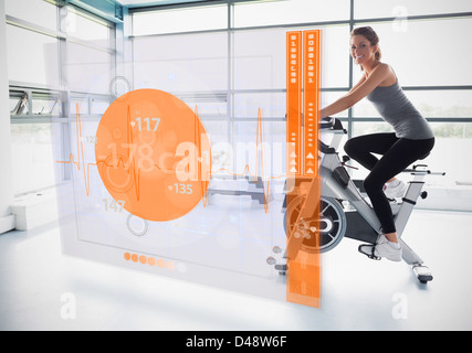 Young girl doing exercise bike with futuristic interface showing calories - Stock Photo