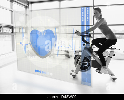 Young attractive girl doing exercise bike with futuristic interface - Stock Photo
