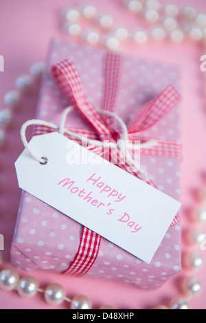 Pink gift wrapped box with mothers day greeting and pearls - Stock Photo