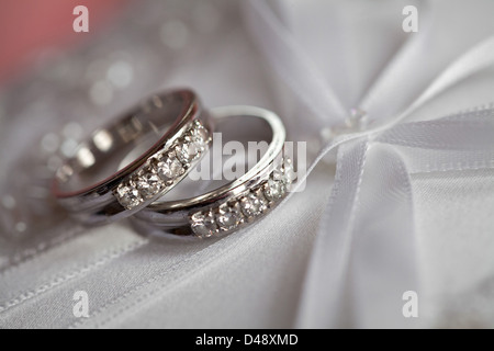 A groom and bride's wedding bands pictured on a ornamental pillow. - Stock Photo