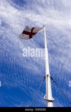 English flag of St George flying at top of flagpole against blue sky - Stock Photo