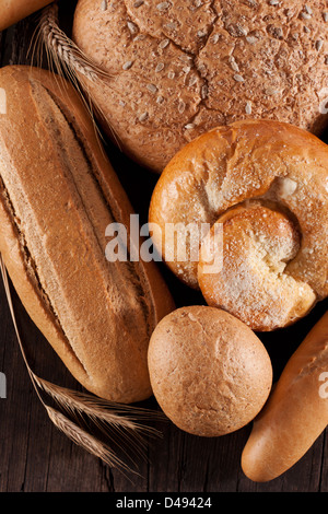 Assortment of baked bread on wooden table - Stock Photo
