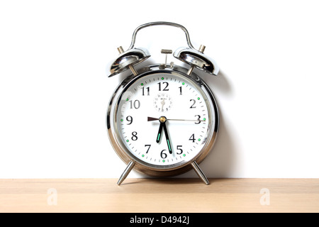 Chrome alarm clock with bells on, set just before 6-30 - Stock Photo