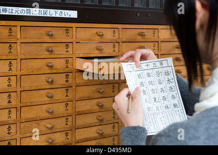 Omikuji paper oracle removed from numbered drawer at Sensoji Temple tells one what the future holds,a good or bad - Stock Photo