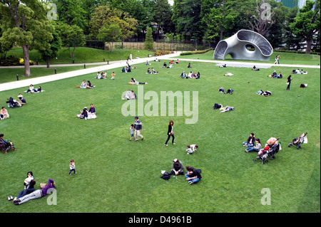 People relaxing on lawn by sculpture at new Tokyo Midtown mixed-use shopping, hotel and residential complex in Roppongi, - Stock Photo