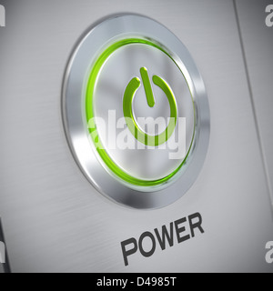 power button on a brushed aluminum panel with a green light and the symbol of energy start, blur effect - Stock Photo