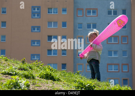 Berlin, Germany, Little girl with pink leg in front of a plate - Stock Photo