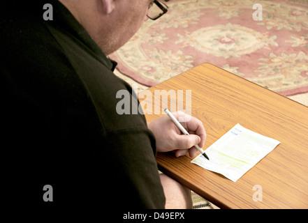 Man filling in back of prescription / prescriptions - Stock Photo