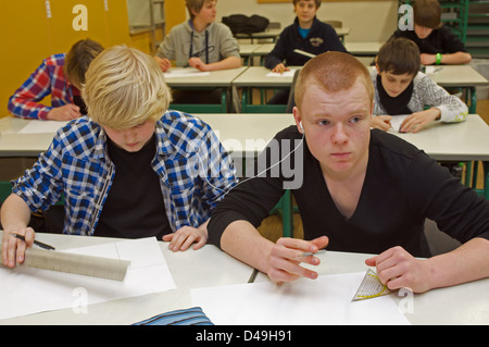 Boys sharing headphones while in a technical drawing lesson - Stock Photo