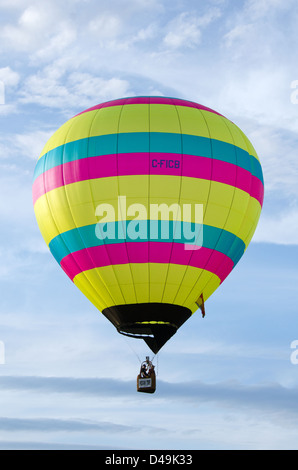 A brightly striped hot air balloon floats past fluffy white clouds. - Stock Photo