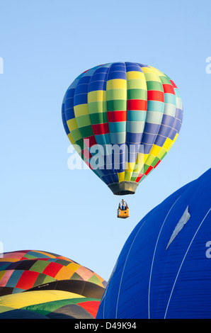 A brightly-coloured hot air balloon rises into a cloudless blue morning sky. - Stock Photo
