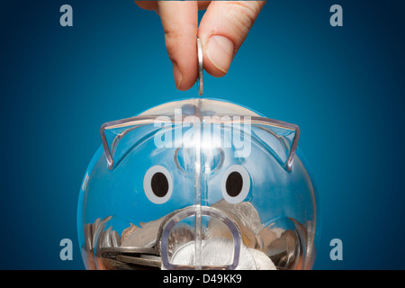 Saving, male hand putting a coin into piggy bank. - Stock Photo