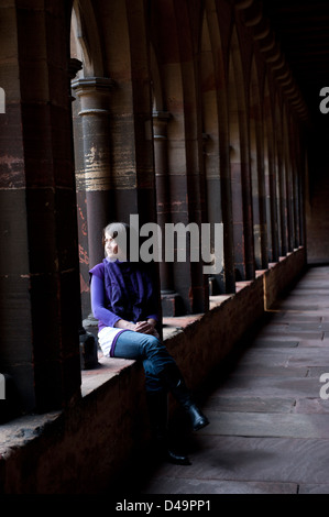 Colmar, France, the woman sitting in the cloister of the Musee d'Unterlinden - Stock Photo