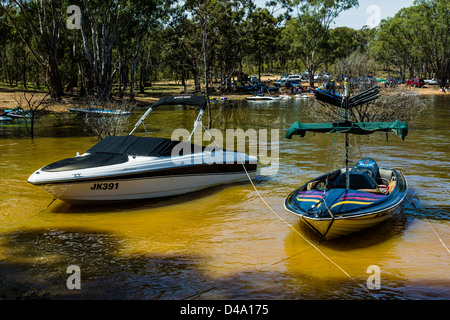 Waterski boats tied up on the shore of Lake Eppalock, Victoria Australia - Stock Photo