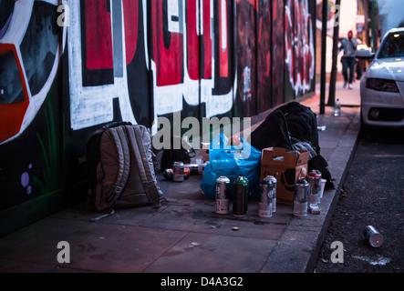 Selection of spray cans and bags alongside graffiti on hoardings along Brick Lane - Stock Photo