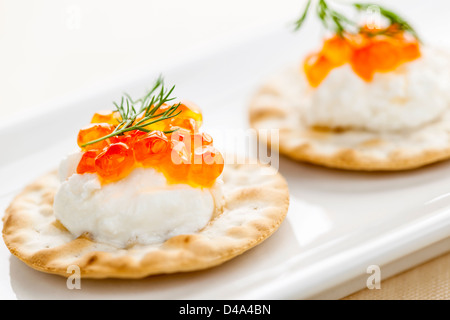 Closeup of caviar and cream cheese appetizer on crackers - Stock Photo