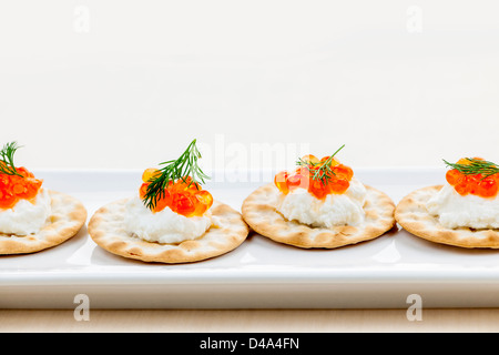 Caviar appetizer with goat cheese and crackers on white plate - Stock Photo