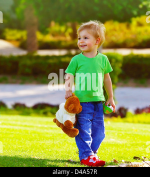 Photo of cute small boy in the park holding teddy bear, adorable child play with soft toy outdoors in spring time, - Stock Photo