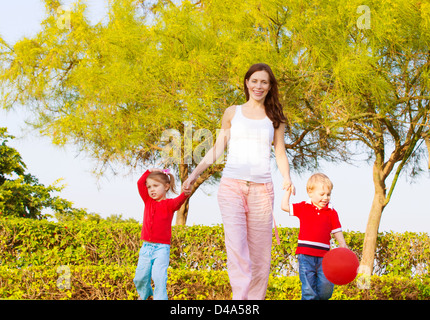 Picture of happy young family in park, cute pregnant mother with two sweet child walking outdoors in spring time, - Stock Photo
