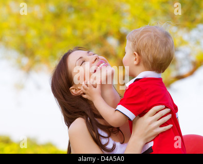 Picture of happy young mother playing game with cute little son outdoors in spring time, cheerful child with mom - Stock Photo