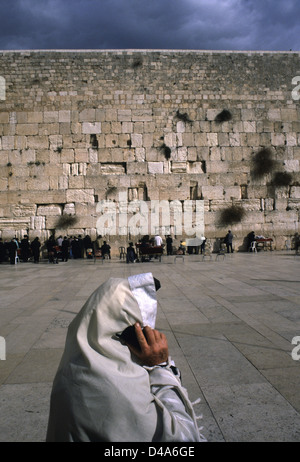 Jewish worshiper with Talit prayer shawl using mobile phone at the Western Wall or Wailing wall in East Jerusalem - Stock Photo