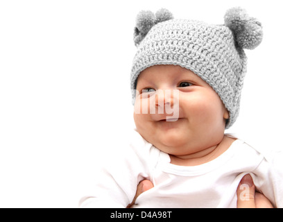 Happy baby in knitted hat in mothers hands - Stock Photo