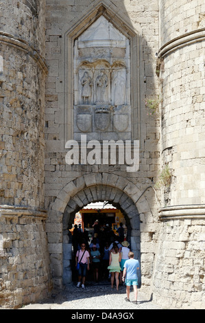 Rhodes. Greece. Tourists walking through the Marine Gate which forms part of the old walled medieval town of Rhodes. - Stock Photo
