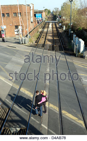 A couple walk across the railway level crossing on Stockbridge Road in Chichester, West Sussex, UK. - Stock Photo