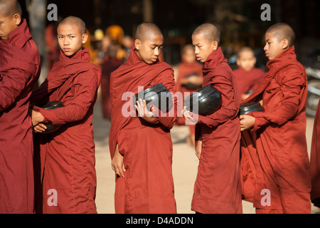 Buddhist monks receiving rice in Bagan rural Burma - Stock Photo
