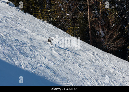 Mountain skier going down from a mountain slope - Stock Photo