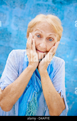 Old blonde woman portrait, lady in elegant clothes with hands on face for joy and surprise on blue background - Stock Photo
