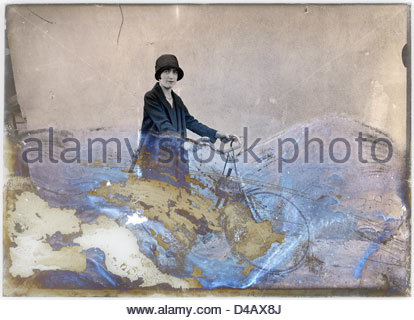 severely eroding glass plate of woman posing with bicycle - Stock Photo