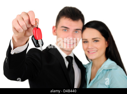 Isolated young business couple with car key - Stock Photo