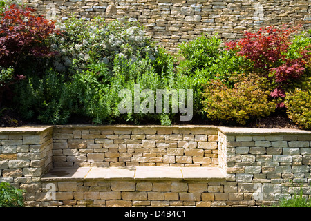A garden seat built into the drystone wall of a raised garden shrubs border bed, Gloucestershire, England, UK - Stock Photo