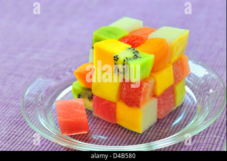 cube fruits salad on lilac background - Stock Photo