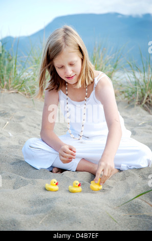 Young girl sitting on beach putting ducks in a row - Stock Photo
