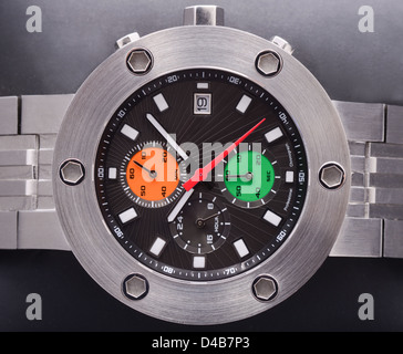 A close up of a chunky steel sports watch with black, orange and green dials - Stock Photo
