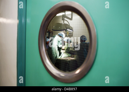 View through operating door window of surgical staff operating on patient - Stock Photo